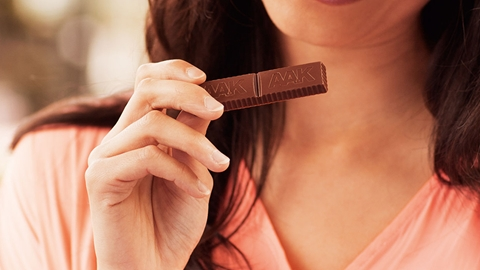 Woman Holding a Piece of Chocolate - Chocolate and Confectionery - AAK