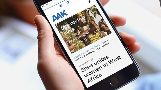 Hand holding a smart phone that displays AAK news article - News & Stories - AAK
