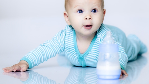 Happy baby on the floor, behind a feeding bottle - Special Nutrition - AAK