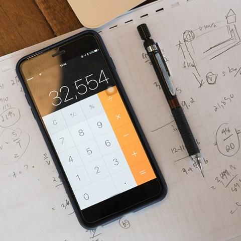 Smartphone, penna och block med beräkningar - Technical Products - AAK