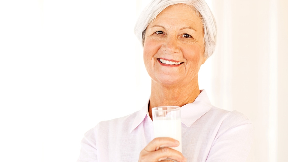 Older woman smiling and holding a glass of milk - Special Nutrition - AAK