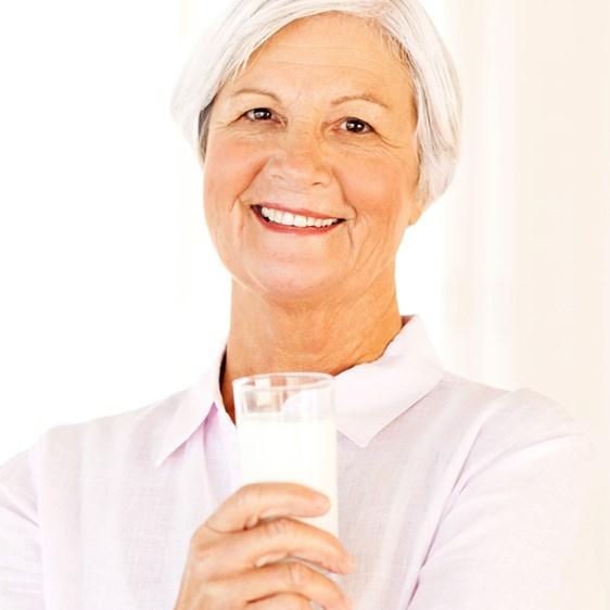 En äldre kvinna som ler och håller ett glas mjölk - Special Nutrition - AAK