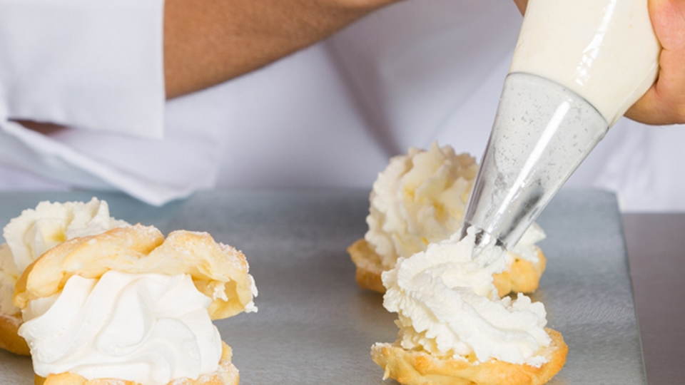 Baker piping cream on cakes - Dairy and Ice cream - AAK