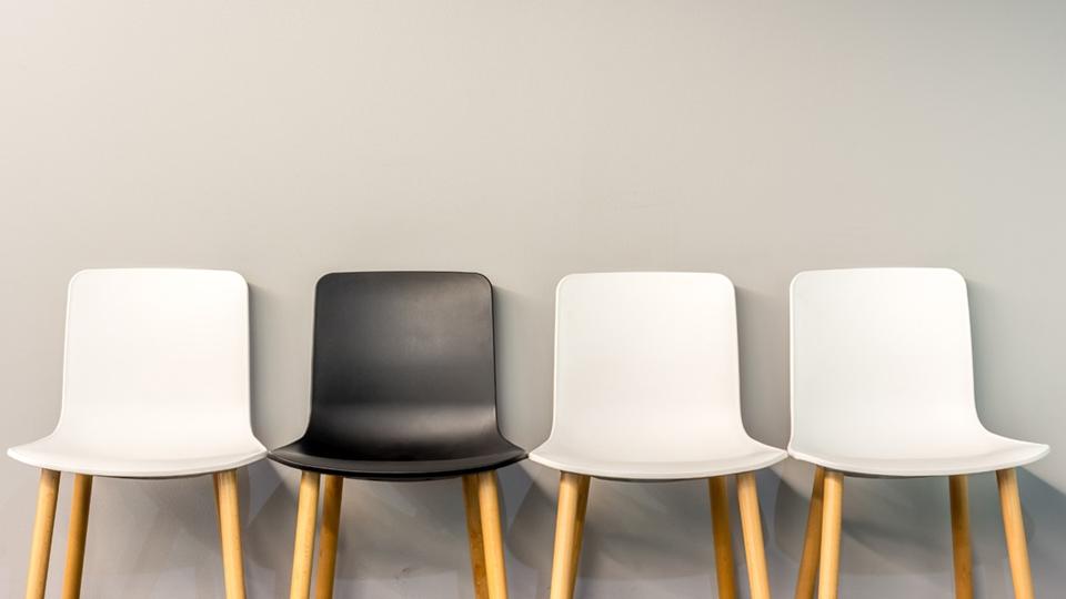 Rad med stolar i olika färger längs en vägg - Investerare - AAK