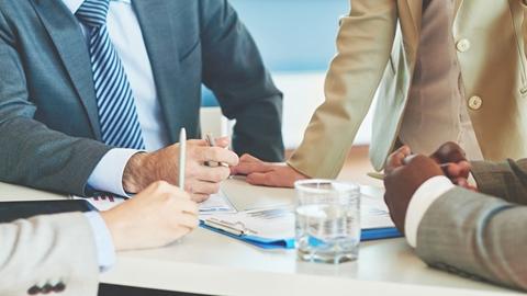 Affärsfolk samlade kring ett bord för att analysera rapporter - Om oss - AAK