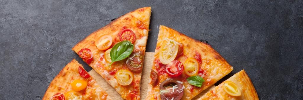Basilika och tomat på läcker pizza som ligger på ett marmorbord - Bageri - AAK