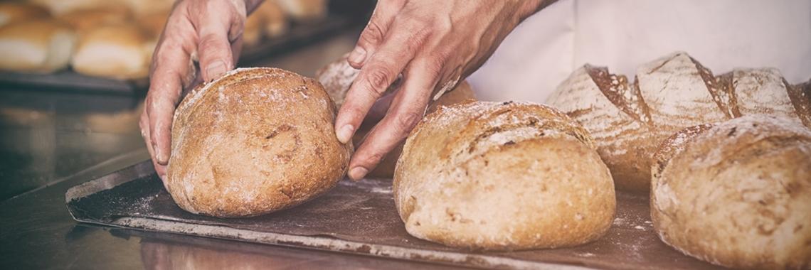 En bagare som tar ut bröd ur ugn - Bageri - AAK