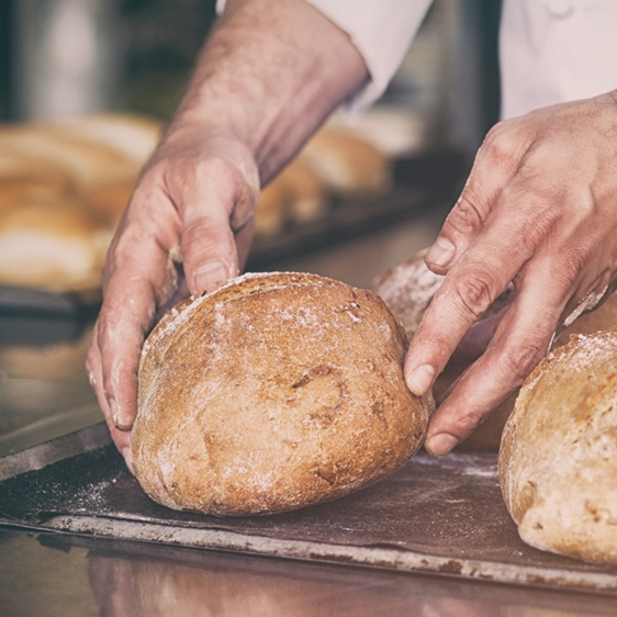 Baker Takes out Loafs of Bread From an Oven - Bakery - AAK