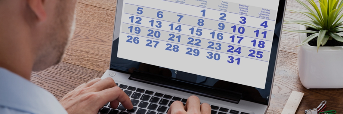Man typing on laptop keyboard and looking at calendar - Investors - AAK
