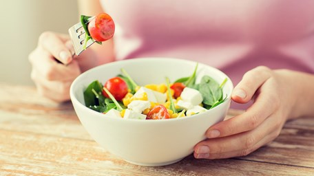 Woman in front a bowl of vegetables and feta cheese - Special Nutrition - AAK