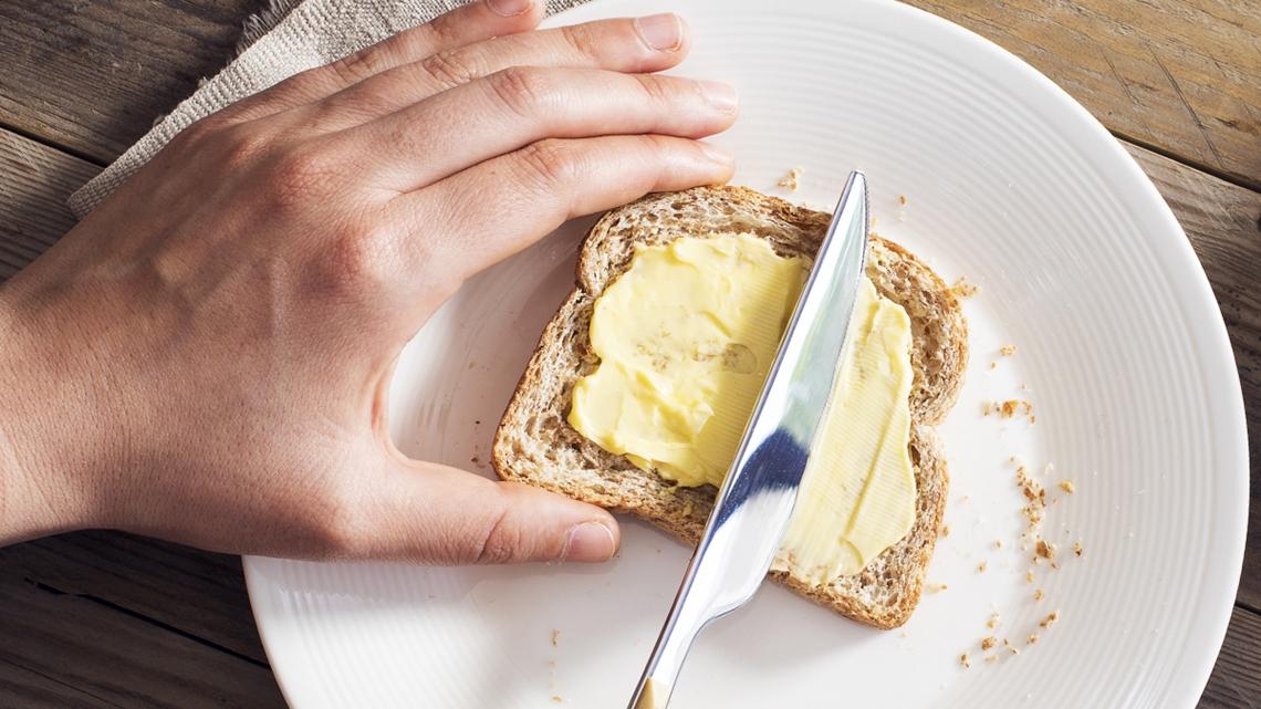 Någon brer smör på en skiva bröd - Mejeriprodukter och glass - AAK