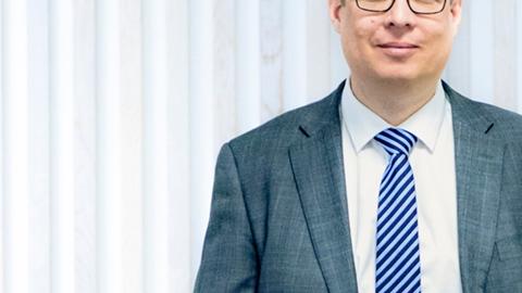 Ekonomichef Fredrik Nilsson står framför vit vägg - Investerare - AAK