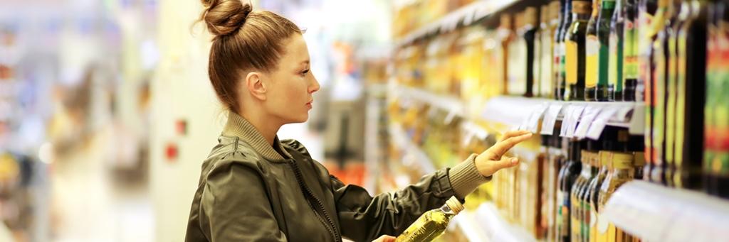 En kvinna tittar på vegetabilisk olja i en affär - Foodservice and Retail - AAK