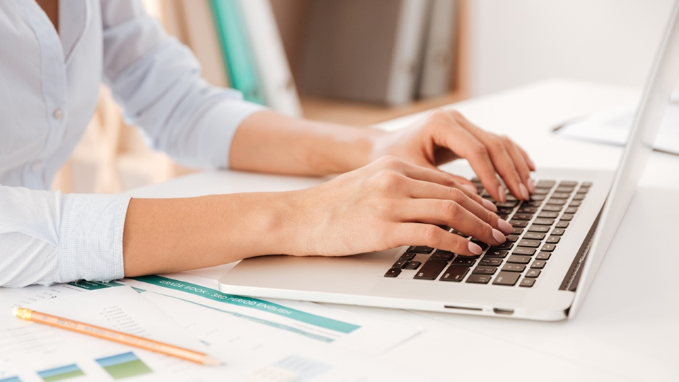 Hands of a woman seen as she types on a laptop - Investors - AAK