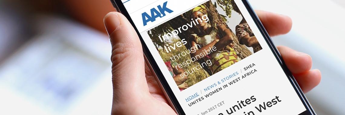 Hand håller smartphone som visar en artikel av AAK - Nyheter och artiklar - AAK